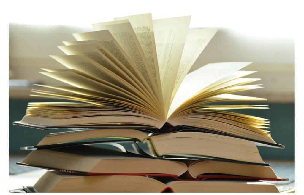 Il y a quatre livres ouverts empilés et un cinquième par-dessus dont les feuilles forment un éventail. Ce sont des manuels et des méthodes scolaires dans un lycée pour revoir la méthode du commentaire de texte.