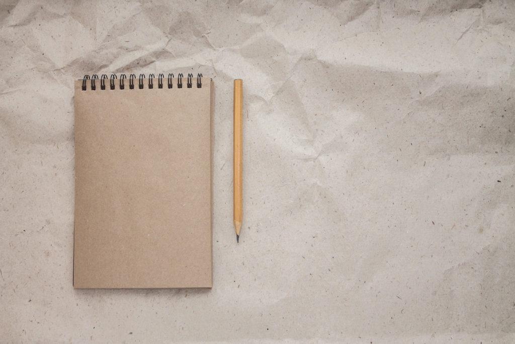 Il y a un carnet de notes ouvert sur une nouvelle page blanche. A côté du carnet se trouve un crayon à papier.Introduction du commentaire peut faire craindre la page blanche.