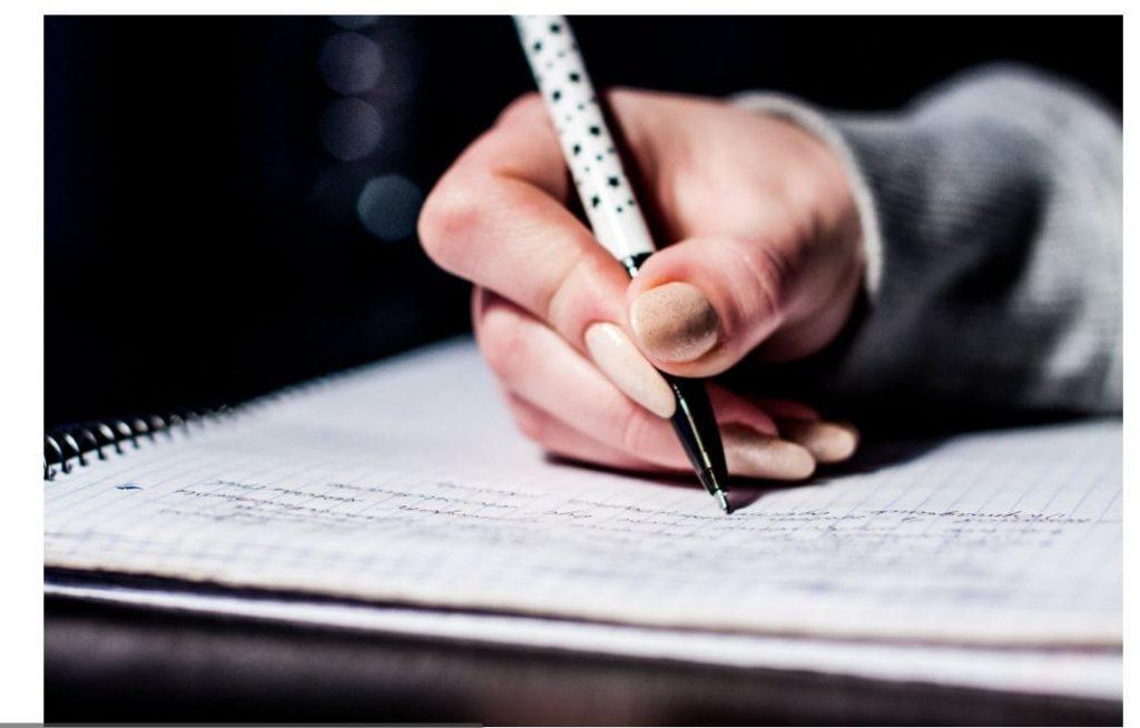On voit une main d'élève écrivant une fiche de lecture sur une feuille de cahier avec un stylo.