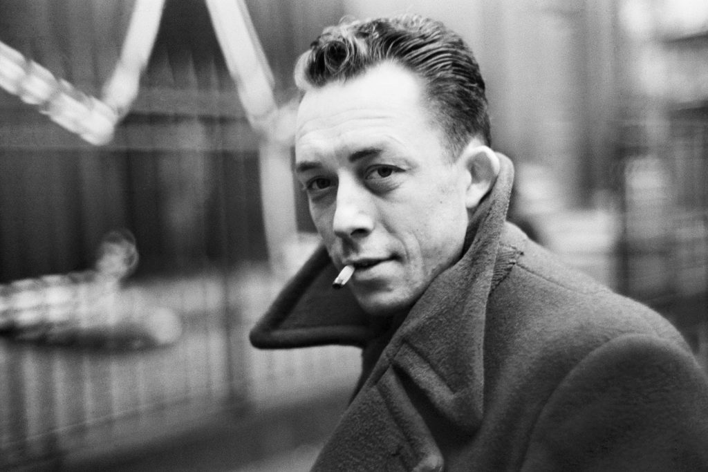 On voit Albert Camus en train de fumer une cigarette.